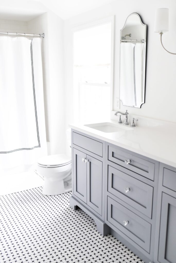 bathroom with shower curtain and blue vanity