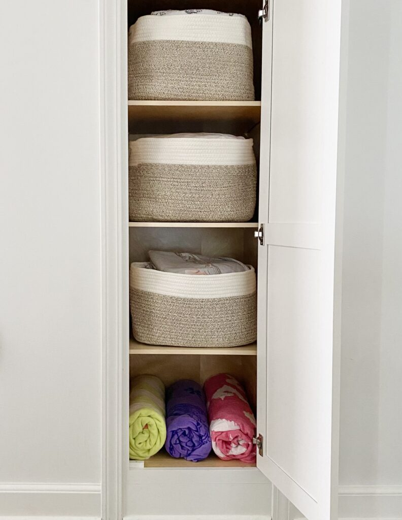 Linen cabinet organized with baskets